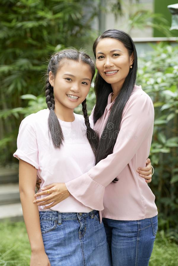 Asian teenage girl with mother. Beautiful adult women and teenage girl embracing with love looking at camera in green garden stock image