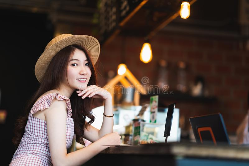 Asian teenage girl smiling in coffee shop with copy space. Cafe culture casual lifestyle, happy traveler woman concept. Portrait of cute and beautiful Asian stock image