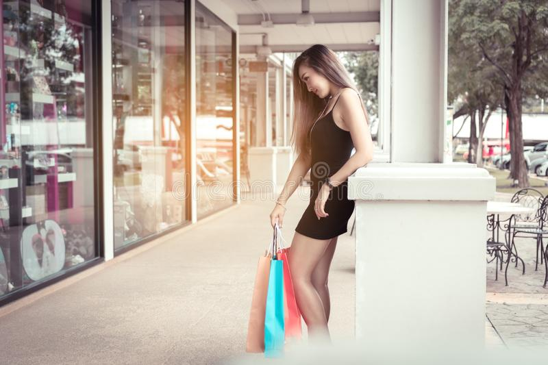 Asian teenage girls standing at poles and holding shopping bags.  stock photos