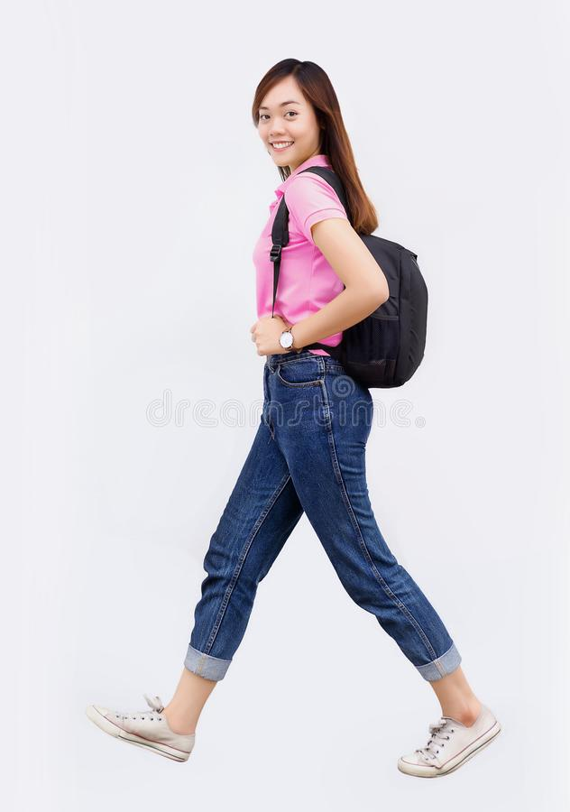 Asian teenage hold backpack belt and walk action on white stock image