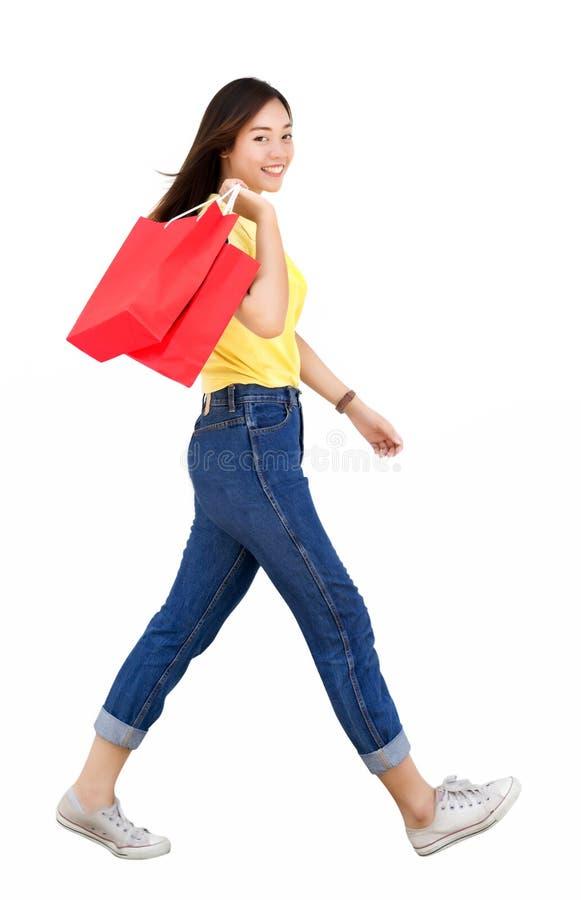 Asian teenage hold shoppping bag and walk action stock photos