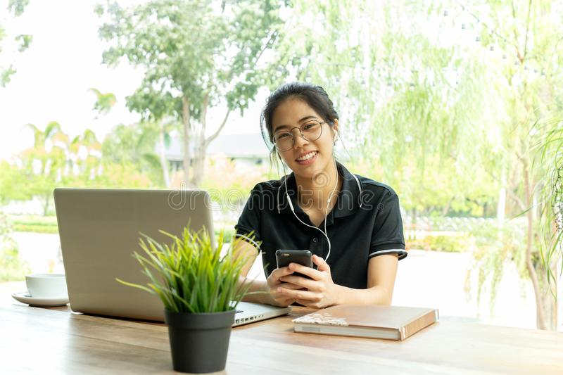 Asian teenage woman with earphone and laptop siting in cafe. stock image
