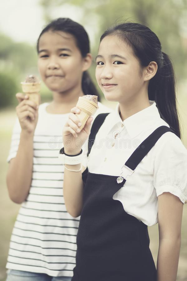 Asian teenager eating icecream cone with happiness face stock images