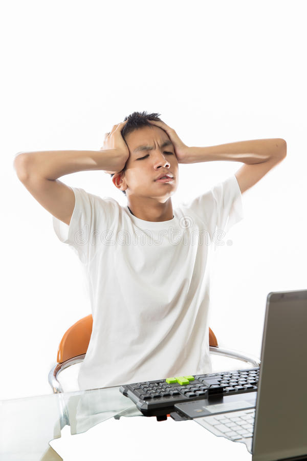 Asian teenager get confuse with computer. Asian teenager using computer and getting confuse with hands on his head royalty free stock photos