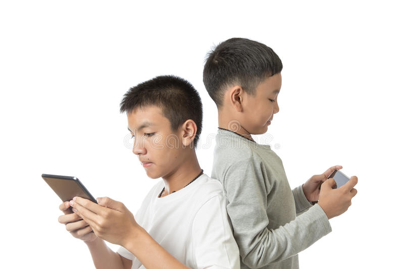 Asian teenager and his brother on tablet and smartphone stock photos