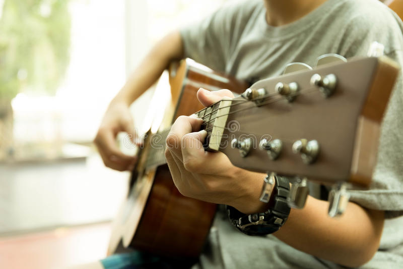 Asian teenager playing the acoustic guitar royalty free stock image