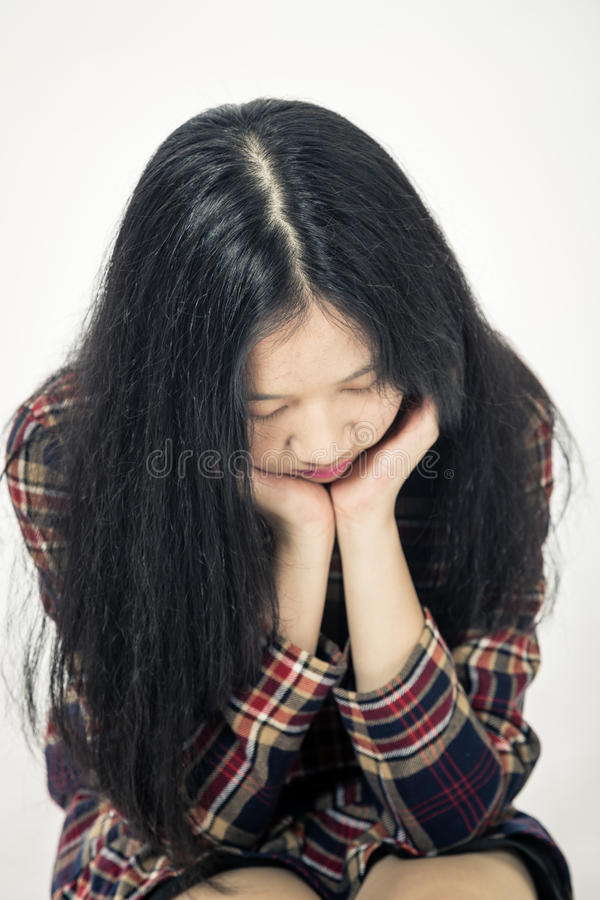 Asian teenager sad with head in hands stock images