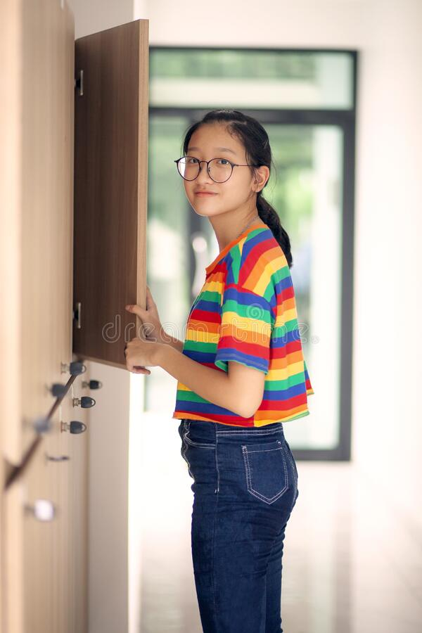 Asian teenager standing at school locker looking with eye contact to camera stock photo
