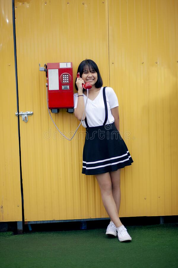 Asian teenager talking to old model of public telephone against yellow sync wall stock photos