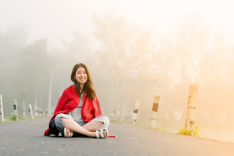 Asian teenager Wearing a red sweater Sitting in the middle of the road by the reservoir In the morning mist And morning sunlight royalty free stock photos