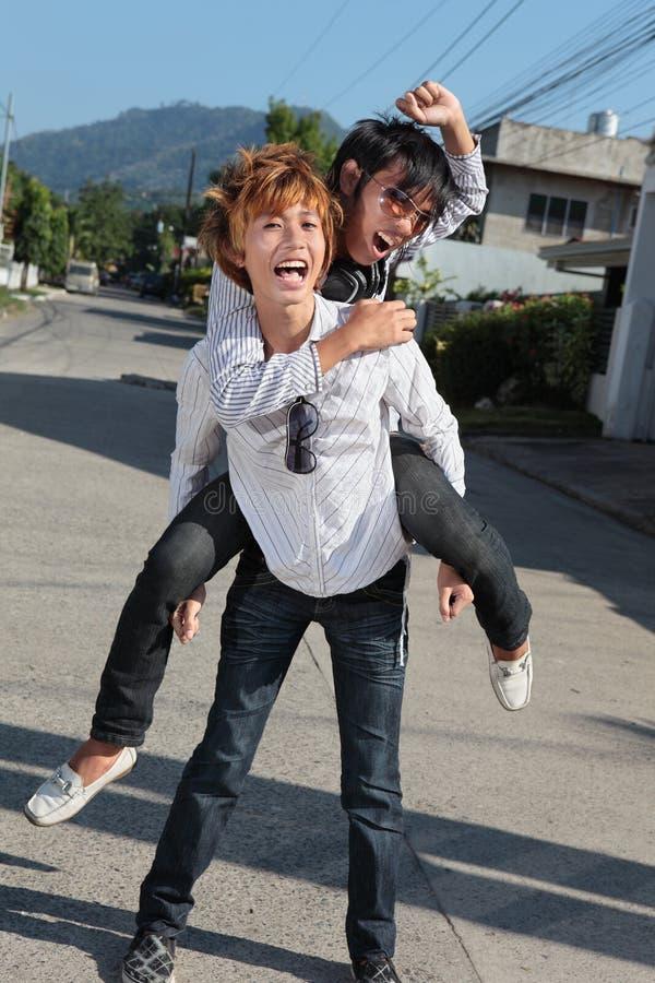 Asian teens piggyback on suburban street stock image