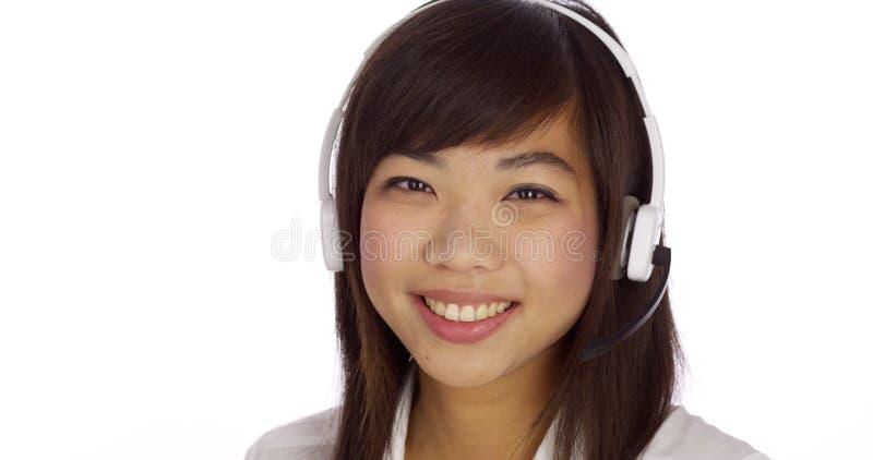 Asian telemarketer looking at camera stock photos