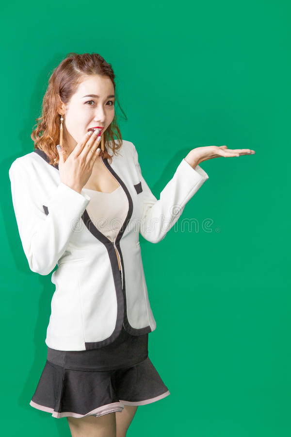 Asian thai girl open hand show product. Asian Thai business look lady open hand to show some product on green screen royalty free stock photo