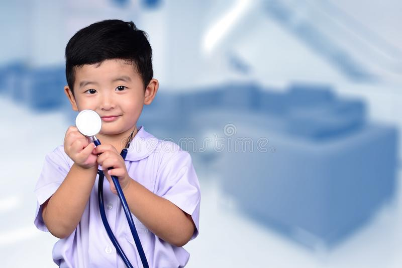 Asian Thai kid with medical stethoscope looking at camera, healthy concept stock photos