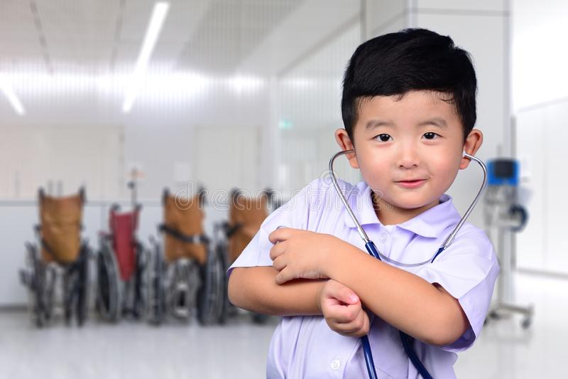 Asian Thai kid with medical stethoscope looking at camera, healthy concept royalty free stock image