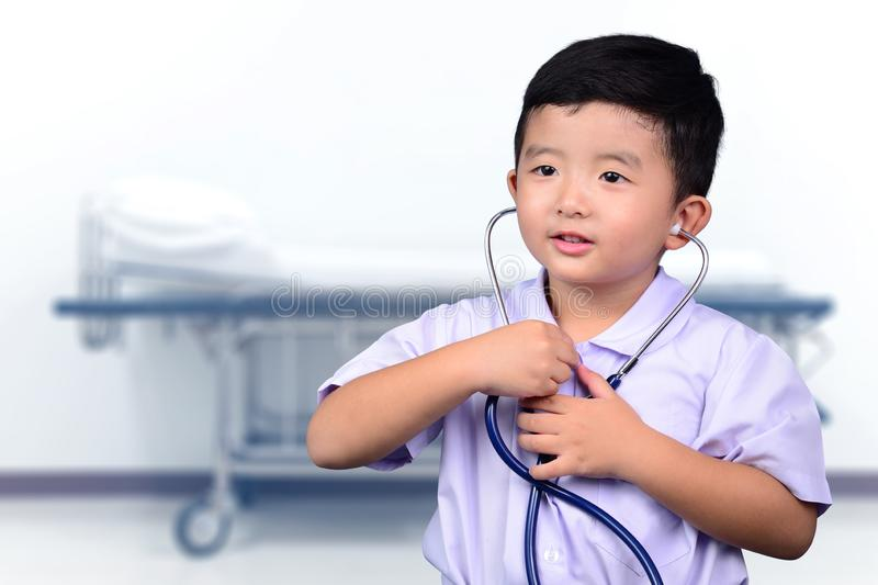 Asian Thai kid with medical stethoscope looking at camera, healthy concept royalty free stock photos