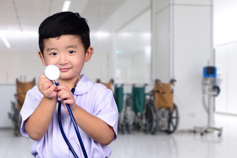 Asian Thai kid with medical stethoscope looking at camera, healthy concept royalty free stock photography