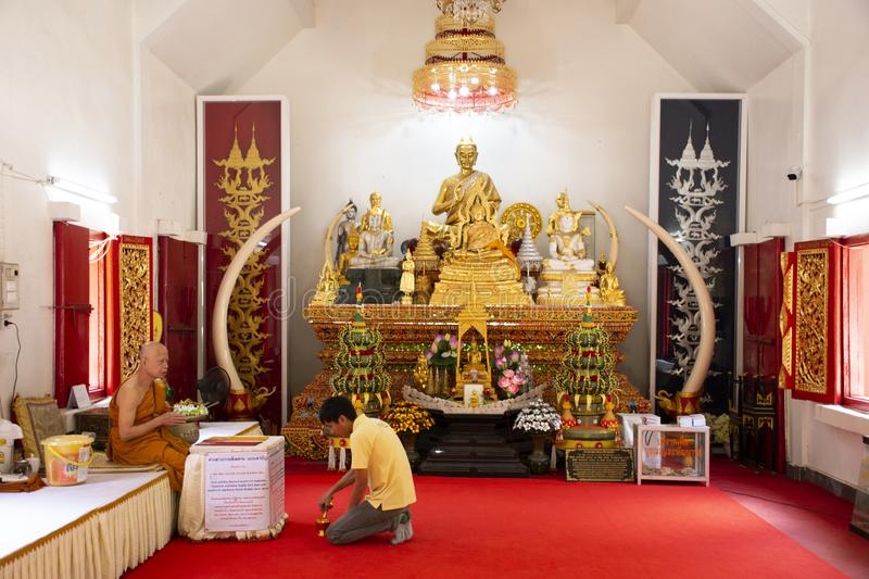 Asian thai man sitting respect praying with monks and buddha statue at Wat Phra That Doi Tung in Chiang Rai, Thailand stock images