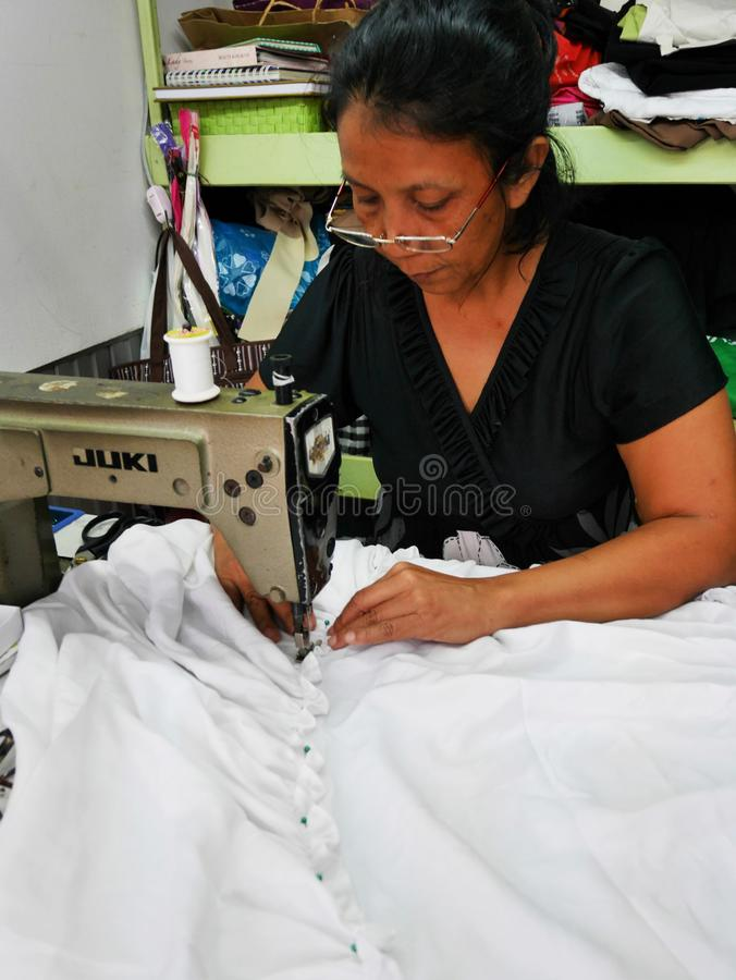 Asian Thai old women use machine sewing and creative design clothes fashion in studio work shop in Nonthaburi, Thailand stock image