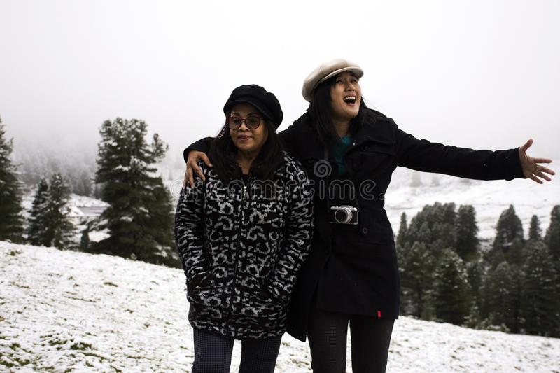 Asian thai people daughter and mother travel and posing for take photo with snow at top of mountain. In Kaunergrat nature park while snowing in Tyrol, Austria stock photography