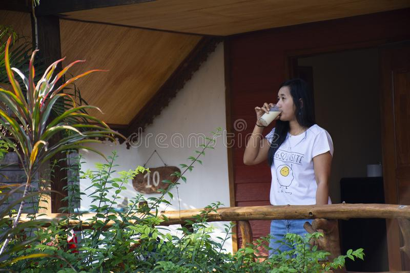 Asian thai woman drinking soy milk on patio of wooden hut of resort and homestay in morning time in Chaiyaphum, Thailand stock image