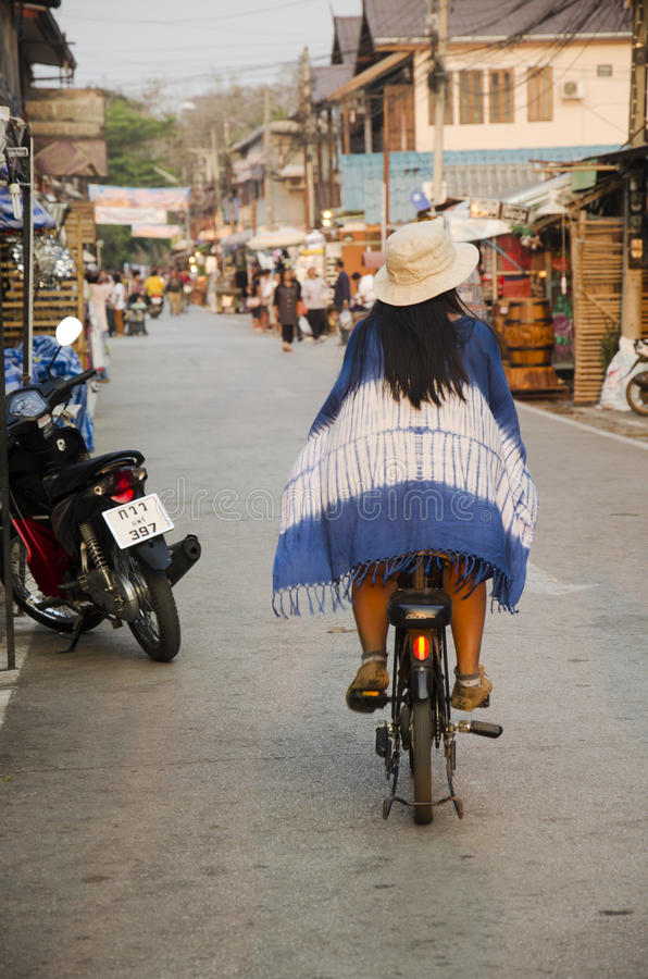Asian thai woman ride bicycle on street night market in small alley at Chiang Khan stock images