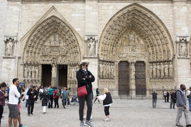 Asian thai woman travel and posing for take photo at Cathedrale Notre-Dame de Paris. Asian thai woman travel and posing for take photo at courtyard of Cathedrale stock photography