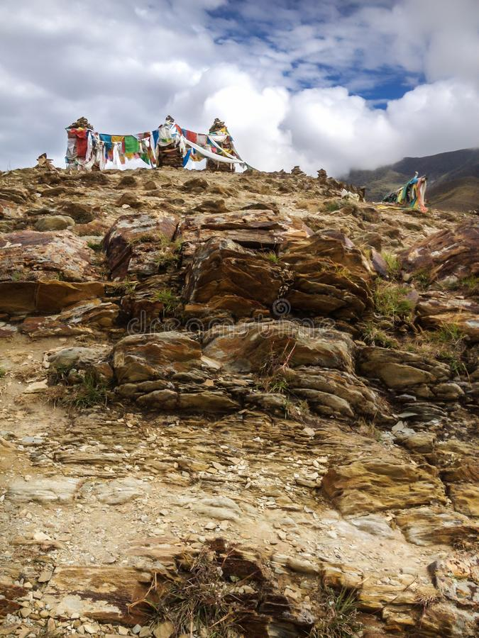Asian Tibetan Buddhist prayer flags on the rocky hill in rural natural background. Nature Travel, tradition, culture and religion. Concept royalty free stock photography