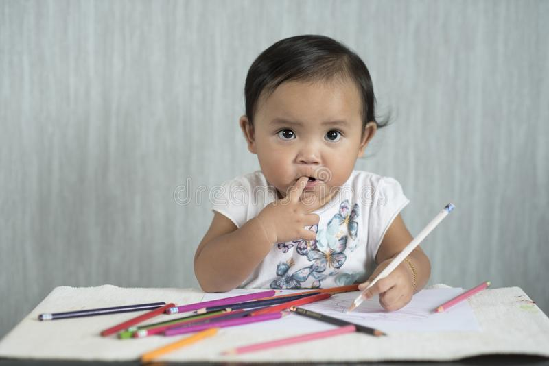Asian toddler / baby girl is having fun learning to use pencils. Education concept. human growth concept stock images
