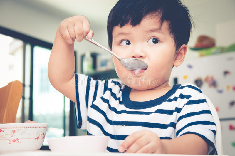 Asian toddler boy eating on high chair.  royalty free stock photos