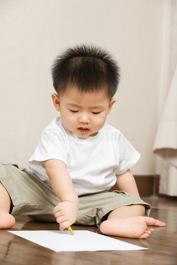 Asian toddler busy drawing. On a paper royalty free stock photo