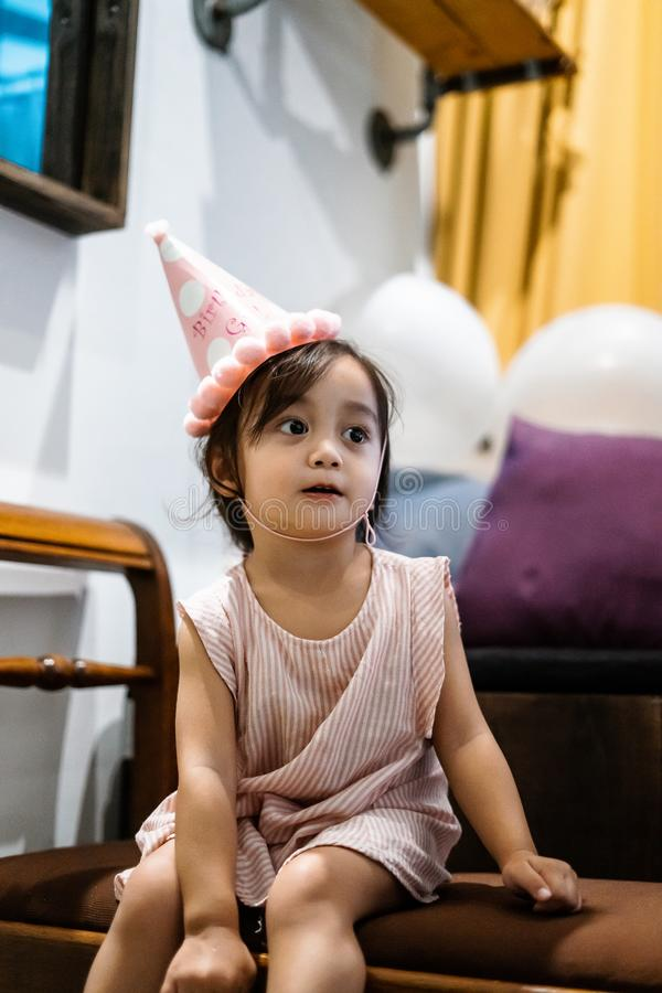 Asian toddler girl is celebrating birthday and wearing a pink hat and holding a baloon. Portrait of Asian toddler girl is celebrating birthday and wearing a pink royalty free stock photos