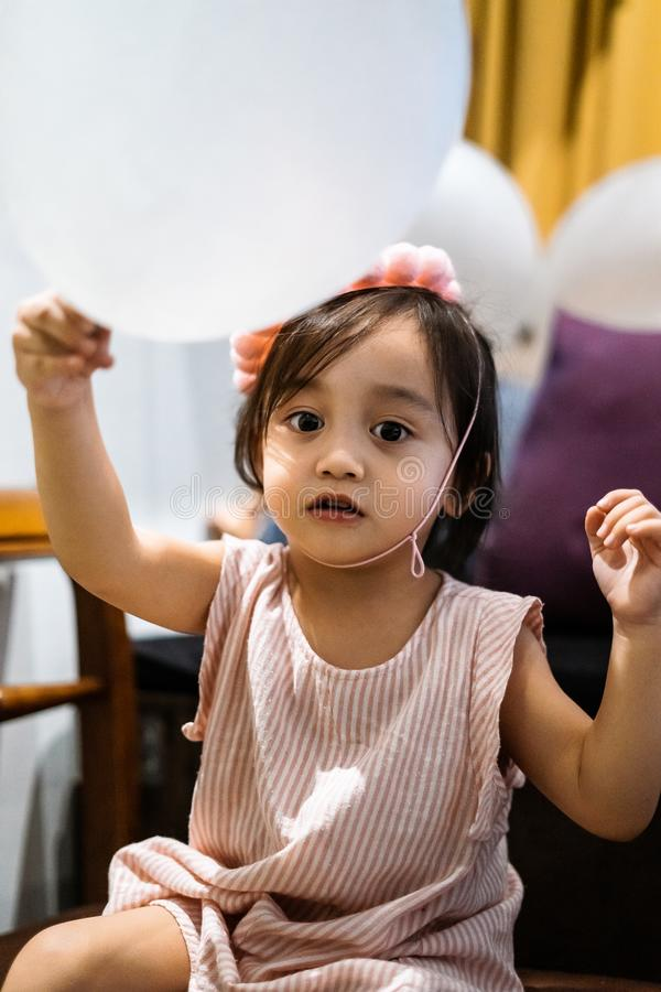 Asian toddler girl is celebrating birthday and wearing a pink hat and holding a baloon. Portrait of Asian toddler girl is celebrating birthday and wearing a pink stock image