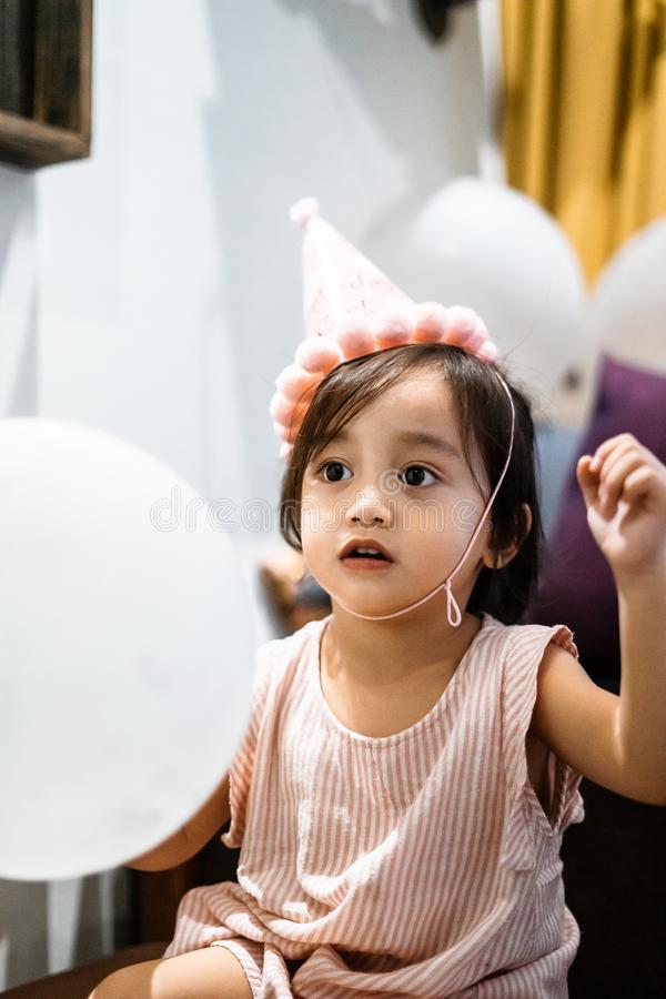 Asian toddler girl is celebrating birthday and wearing a pink hat and holding a baloon. Portrait of Asian toddler girl is celebrating birthday and wearing a pink royalty free stock photography
