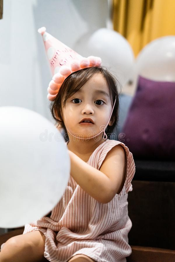 Asian toddler girl is celebrating birthday and wearing a pink hat and holding a baloon. Portrait of Asian toddler girl is celebrating birthday and wearing a pink royalty free stock images