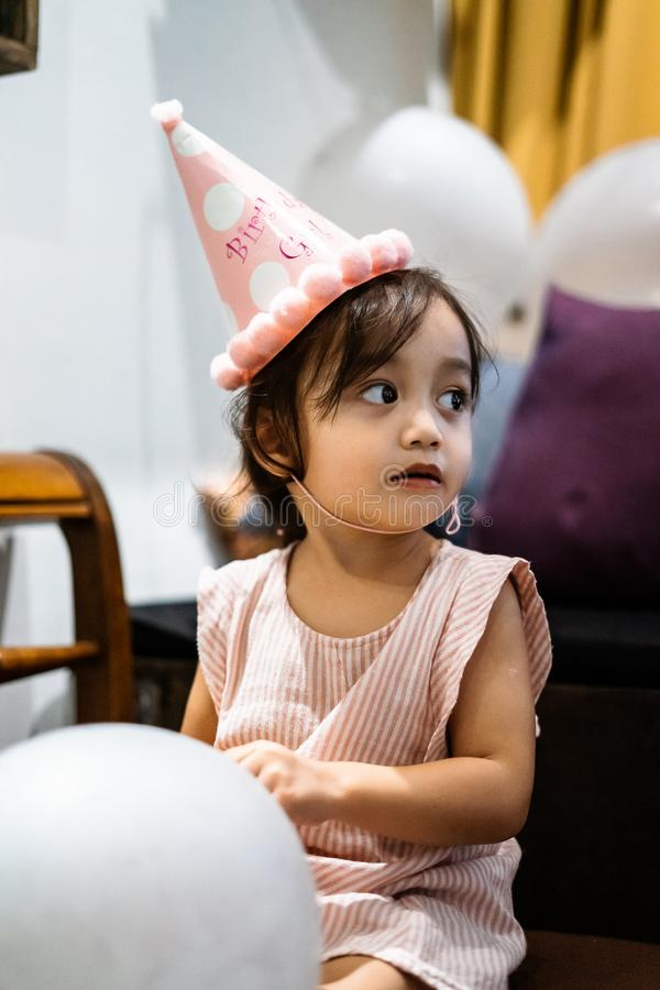 Asian toddler girl is celebrating birthday and wearing a pink hat and holding a baloon. Portrait of Asian toddler girl is celebrating birthday and wearing a pink stock images