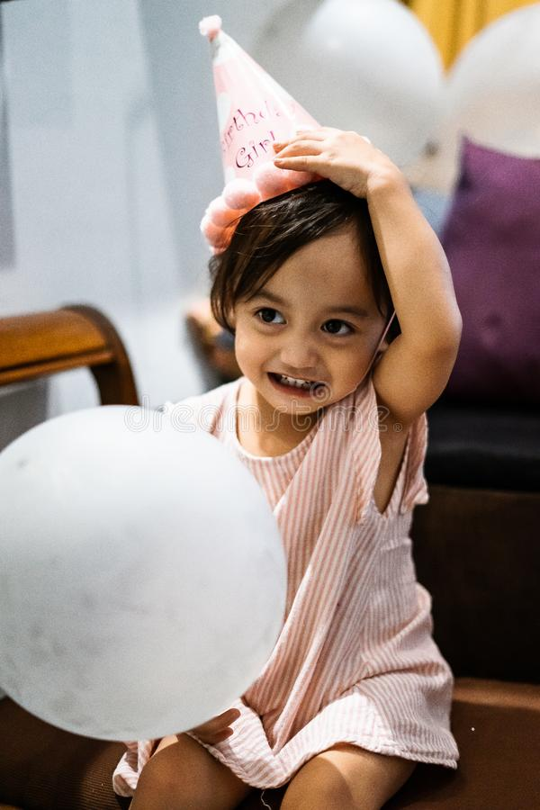 Asian toddler girl is celebrating birthday and wearing a pink hat and holding a baloon. Portrait of Asian toddler girl is celebrating birthday and wearing a pink royalty free stock image