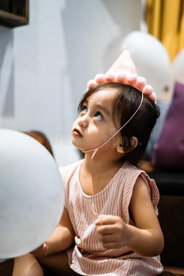 Asian toddler girl is celebrating birthday and wearing a pink hat and holding a baloon. Portrait of Asian toddler girl is celebrating birthday and wearing a pink stock photo