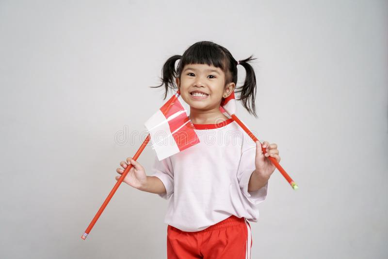 Asian toddler with indonesian flag smiling to camera. Over white background stock images