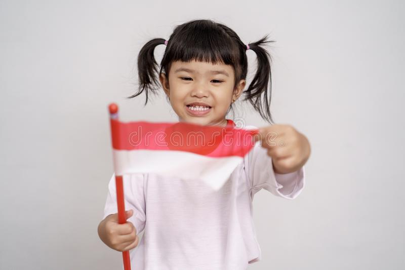 Asian toddler with indonesian flag smiling to camera. Over white background royalty free stock photo