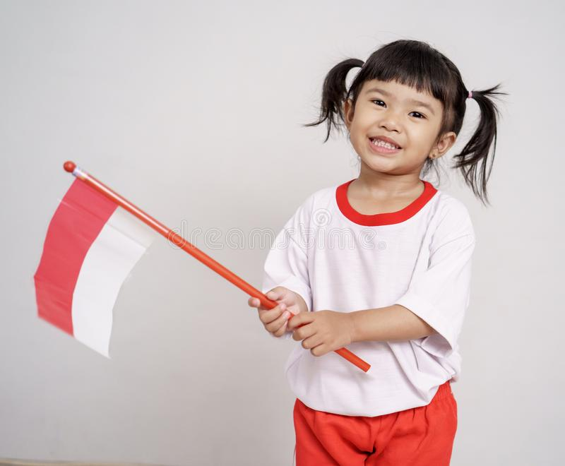 Asian toddler with indonesian flag smiling to camera. Over white background royalty free stock photography