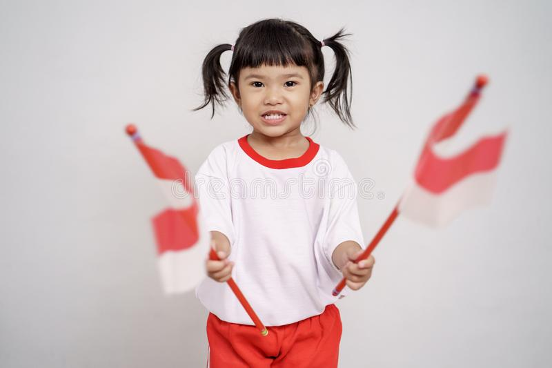 Asian toddler with indonesian flag smiling to camera. Over white background stock photo