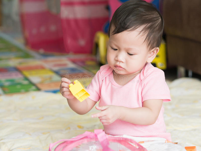 Asian toddler playing puzzle toys alone in house. stock photo