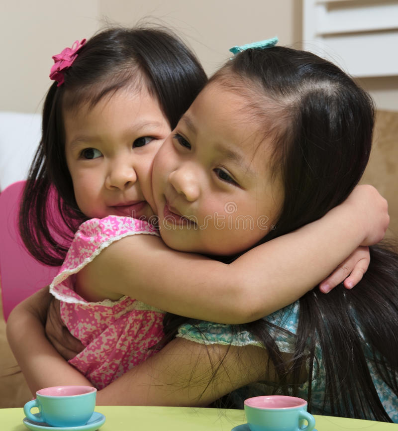 Asian toddler sisters hugging. Sisters are located at home and surrounded by toys and furniture royalty free stock photography