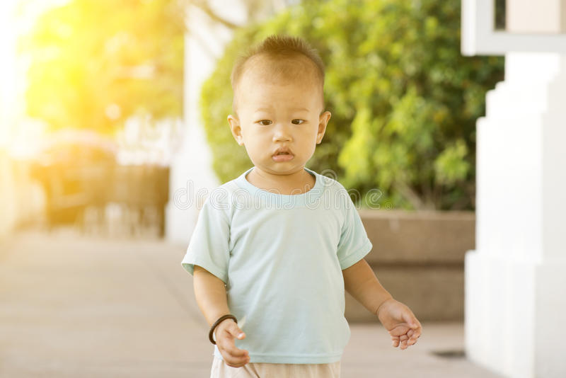 Asian toddler walking at outdoor. Portrait of Asian toddler walking outdoor in sunset royalty free stock photography