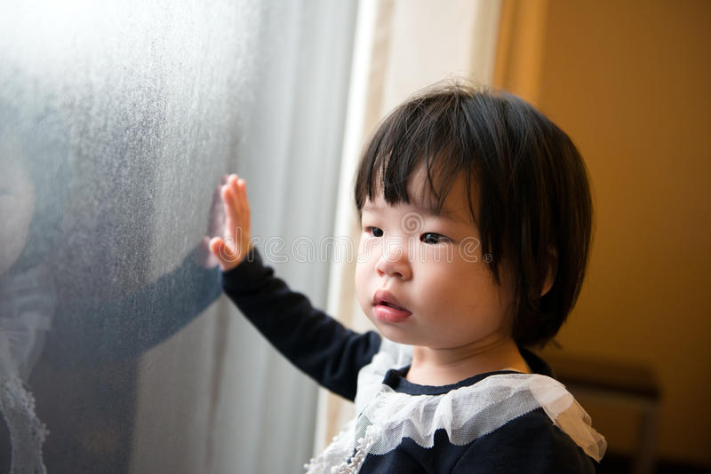 Asian toddler watching the snow. Adorable Asian toddler watching the snow through window stock image