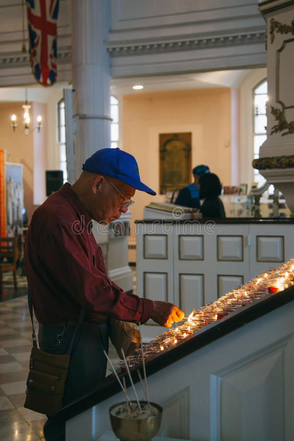 Asian Tourist lighting a candle for the September 11 victims. NEW YORK - JUNE 11: Asian Tourist lighting a candle for the September 11 victims inside the Trinity royalty free stock photography