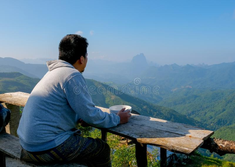 Asian tourist man stay at balcony of some resort and have breakfast in bowl and he look happy and relax stock photography