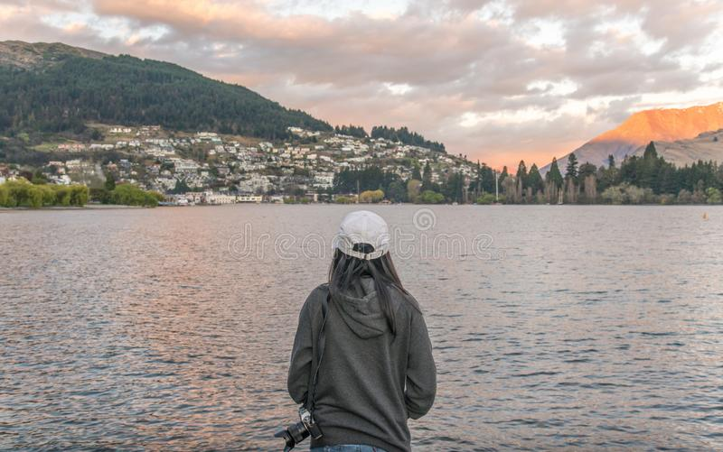 Asian tourist standing in front of the Lake Wakatipu and looking to Queenstown city, New Zealand. Queenstown most tourist attraction city in South Island of New stock images