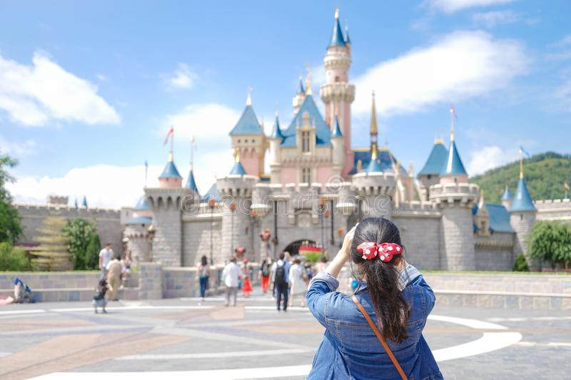 Asian tourist is taking a photo in front of a Disneyland castle in Hong Kong royalty free stock images